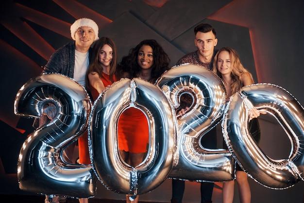 新しい2020年が来ています。パーティーで楽しい多国籍の若者のグループ。明けましておめでとうございます
