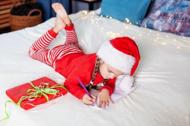 Счастливого рождества. новый год 2020! маленькая девочка в красной пижаме и шапке санта-клауса пишет письмо деду морозу в спальне
