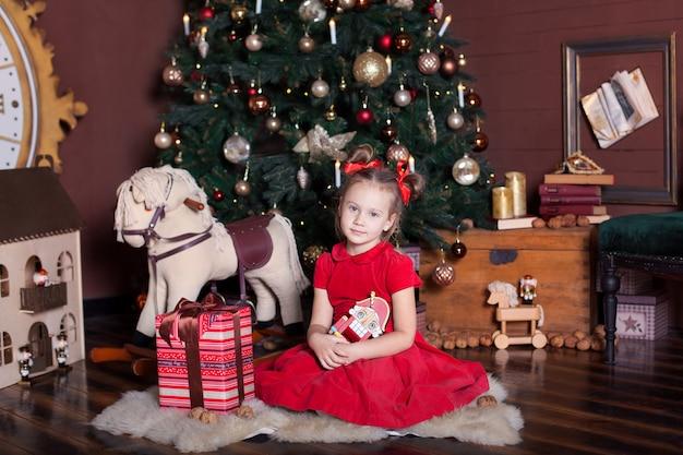 Новый год 2020. счастливого рождества, веселых праздников. маленькая девочка в красном платье держит винтажную деревянную игрушку щелкунчика около классической рождественской елки дома. балерина с щелкунчиком в канун нового года.