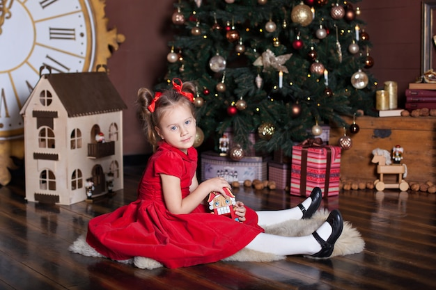Новый год 2020. счастливого рождества, веселых праздников. маленькая девочка в красном винтажном платье сидит возле украшенной елки с деревянной игрушкой щелкунчик. семейный отдых. счастливый малыш наслаждается праздником.