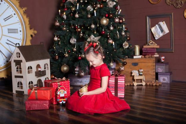 Новый год 2020. счастливого рождества, веселых праздников. портрет маленькой девочки с свечой. маленькая девочка держит свечу в ее руках перед рождественской елкой и подарками. рождественский декор для дома, новогодняя комната