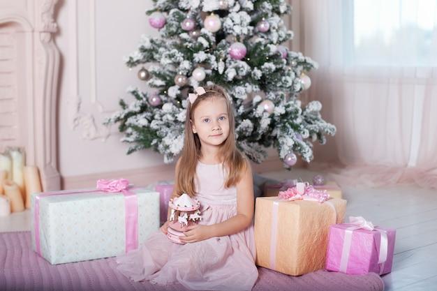 新年2020!クリスマス、休日、幼年期の概念。ピンクのドレスを着た少女は、クリスマスツリーの近くに音楽グッズカルーセルを保持しています。子供はホリデーギフトを受け取りました。大晦日。