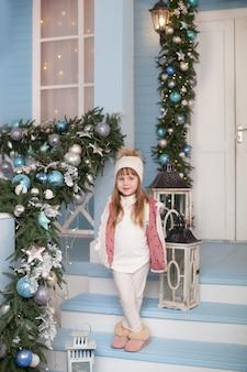 メリークリスマス、ハッピーホリデー! 2020年の新年。クリスマスの装飾が施された家のポーチに立っている少女。子供は新年のテラスを飾ります。花輪のあるクリスマス装飾の屋外テラス。