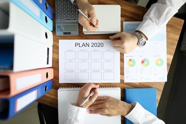 ビジネスマンおよびビジネスウーマンが作業計画を立てる2020