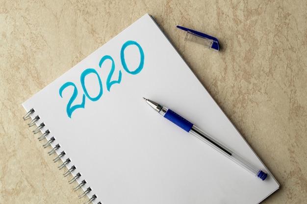 白いノートと青い碑文2020。紙の上の青いペンとテーブルの上のキャップ