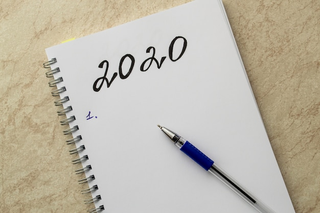 白いノートと黒の碑文2020。紙の上の青いペンとテーブルの上のキャップ