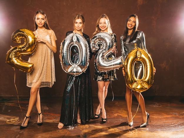 Красивые женщины празднуют новый год. счастливые великолепные девушки в стильных сексуальных вечерних платьях, держа золотые и серебряные воздушные шары 2020 года, развлекаясь на канун нового года. праздник праздник. очаровательные модели