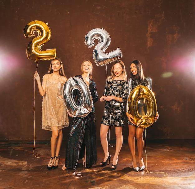 Красивые женщины празднуют новый год. счастливые великолепные девушки в стильных сексуальных платьях, держа золотые и серебряные воздушные шары 2020 года, развлекаясь на канун нового года.