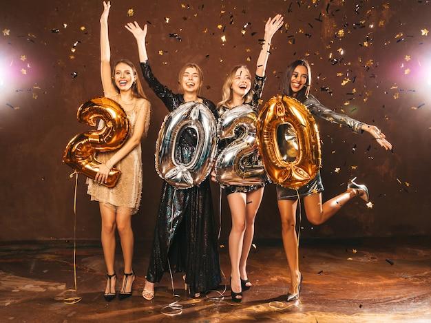 Красивые женщины празднуют новый год. счастливые великолепные девушки в стильных сексуальных вечерних платьях, держа золотые и серебряные воздушные шары 2020 года, развлекаясь на канун нового года. праздник праздник. поднимаем руки