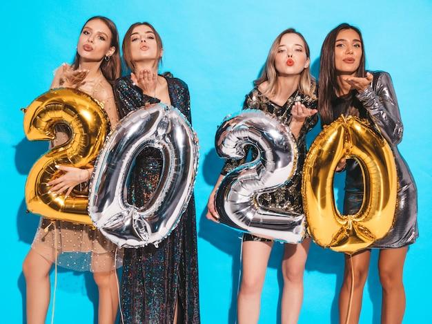 金と銀の2020年風船を保持しているスタイリッシュなセクシーなパーティードレスで幸せな豪華な女の子