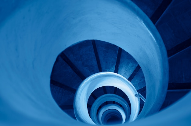 クラシックブルーのトーンのらせん階段の古い階段-2020年の色