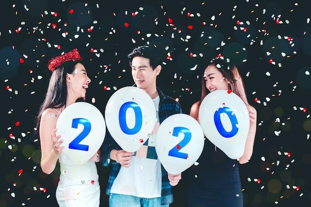 2020新年パーティー、バルーンを保持しているアジアの若い人々のお祝いパーティーのグループ
