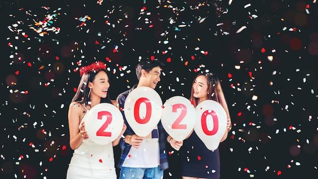 2020ニューイヤーパーティー、バルーンを保持しているアジアの若い人々のお祝いパーティーのグループ