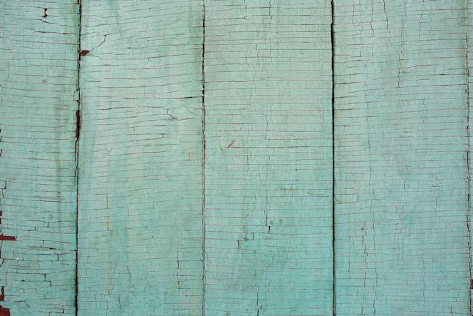 明るい彩度の低い緑、ミント色の古いストレス、風化、ひびの入ったロシア語の塗られた外装木材板無地の背景のテクスチャ。 2020年のトレンドカラー。
