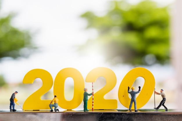 Миниатюрные люди: рабочий бригады строит деревянный номер 2020