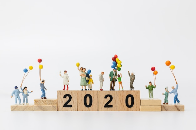 ミニチュアの人々:木製ブロック番号2020にバルーンを保持している幸せな家族