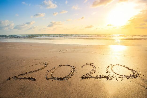 Счастливый новый год 2020 текст на красивом морском пляже с волной рано утром восход над горизонтом