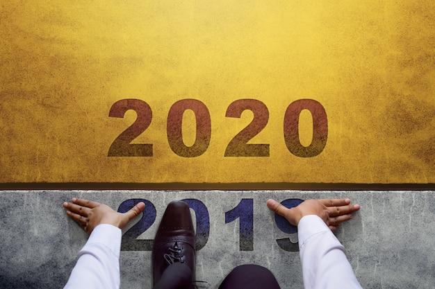 2020年のコンセプト。新しいビジネスチャレンジの準備ができて、スタートラインのビジネスマンのトップビュー
