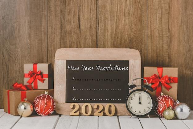 2020 деревянный текст и будильник с рождественскими украшениями и списком новогодних решений написано на доске