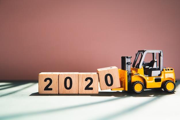 Миниатюрный вилочный погрузчик поднимает деревянный блок 2020 года, используя как концепцию бизнеса и промышленности