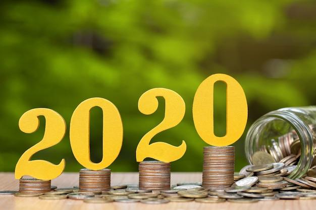 積み上げられたコインの2020年の木製の数字は、金融の成長を示し、お金を節約します。