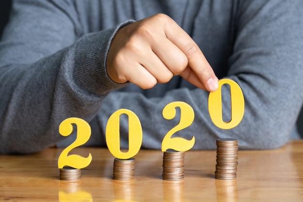 コインのスタックにゴールドの木製数2020を置く女性の手。