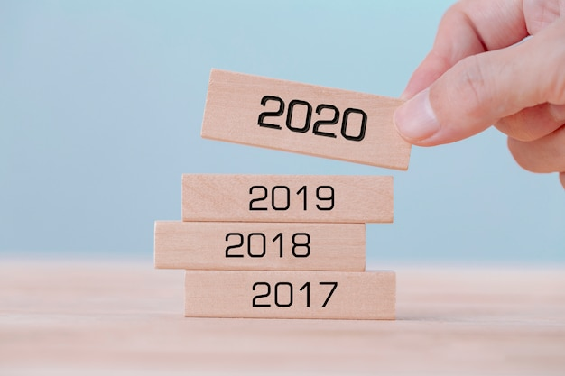 Рука холдинг выбирает деревянные кубики со словом 2020