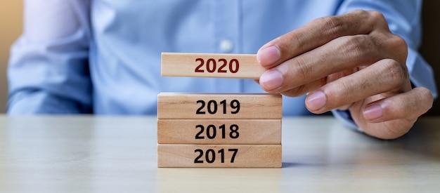 表の背景に2020年の木製のビルディングブロックを引っ張る手