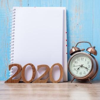 2020新年あけましておめでとうございます、空白のノートブック、レトロな目覚まし時計、木製の番号。