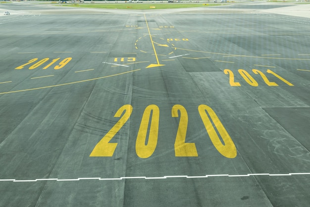 Знак номера 2020 на взлетно-посадочной полосе аэропорта показывает скорый новогодний прием.