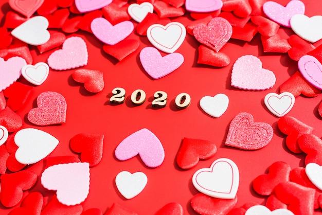 2020 год празднует день святого валентина на красном фоне, наполненном любовными сердцами.