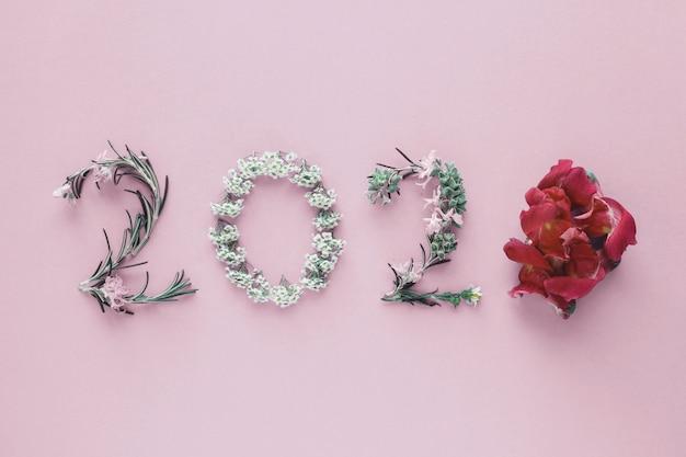 ピンクの背景、新年あけましておめでとうございます、健康的なライフスタイルの自然な葉と花から作られた2020