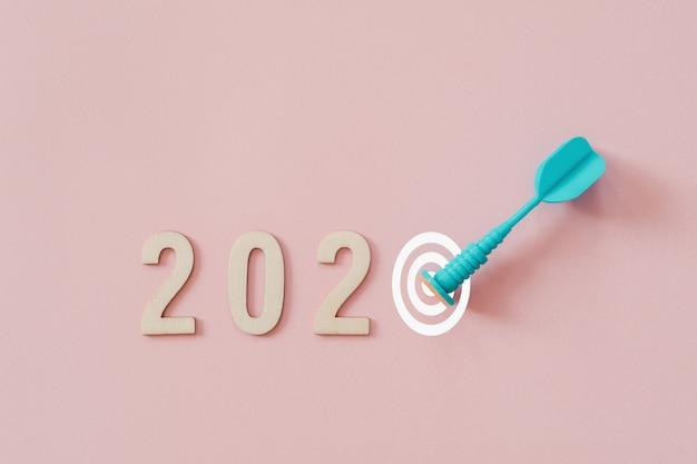 ピンクの背景にターゲットを打つ青いダーツの矢で2020