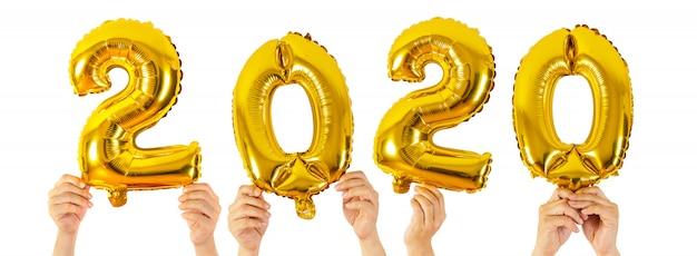 白、新年あけましておめでとうございますに分離された2020番号風船を保持している手