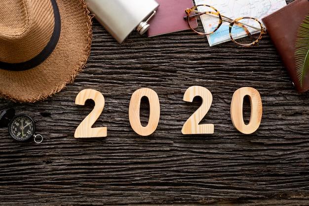アドベンチャーアクセサリーアイテムと木製のテーブルのトップビュー2020新年あけましておめでとうございます番号