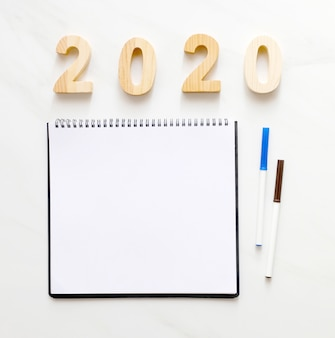 2020年の木製の手紙とテキスト新年背景バナーコンセプトのコピースペースを持つ空白のノートブック紙