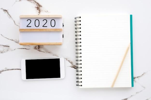 白い大理石の背景に空白の画面を持つ2020木製ボックス空白のノートブック紙スマートフォン