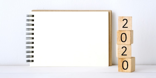 2020の木製キューブとテーブルと白セメント壁背景に空白のノートブック紙