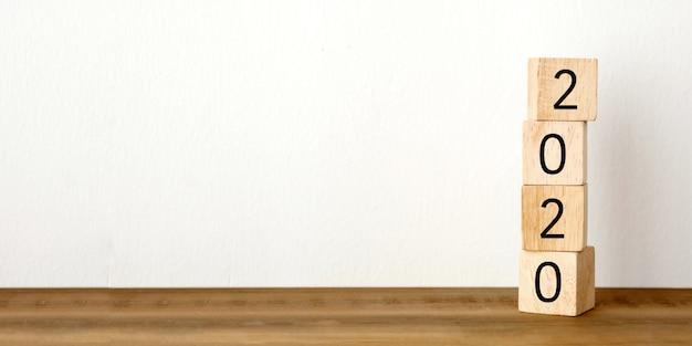 テーブルと白いセメントの壁に2020年の木製キューブ