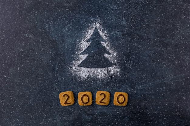 暗い背景にクッキーの数字2020と小麦粉シルエットクリスマスツリー