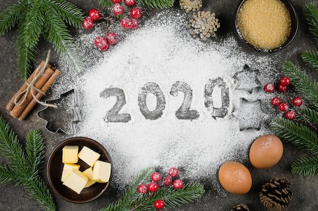 ベーカリーの食材とお祝いの装飾が施された小麦粉で作られた2020年のテキスト