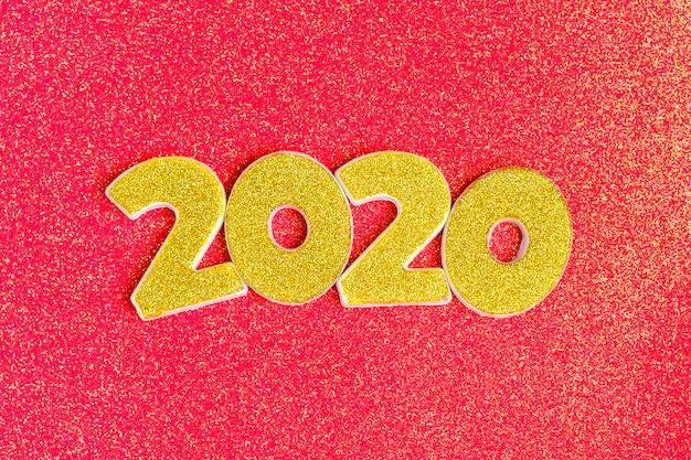 光沢のあるサンゴレッドに金のスパンコールで飾られた2020年の数字。