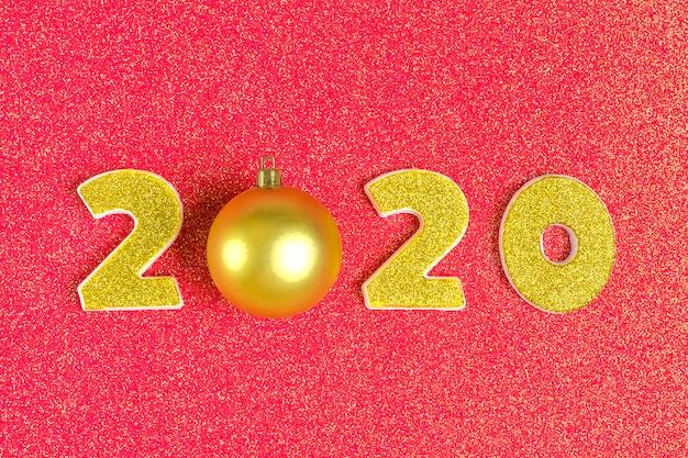 金色のスパンコールで飾られた2020年の数字、光沢のあるコーラルレッドのボール。