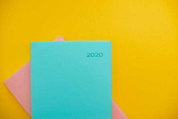 黄色の抽象的な背景に2020メモ帳