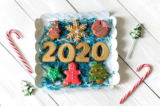 Коробка с фигурками пряников 2020 года и другими традиционными рождественскими сладостями. конфета, круглая снежинка и рыжий человечек, звездный леденец. вид сверху. квартира лежала. рождественская концепция