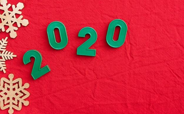 Надпись 2020 на красном фоне рождества. квартира лежала. вид сверху. копировать пространство