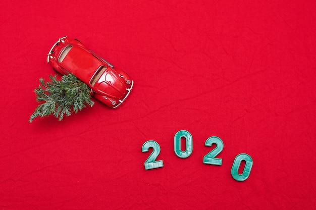 クリスマスツリー、碑文2020と赤いおもちゃの車。赤いクリスマス背景。フラット横たわっていた、トップビュー。