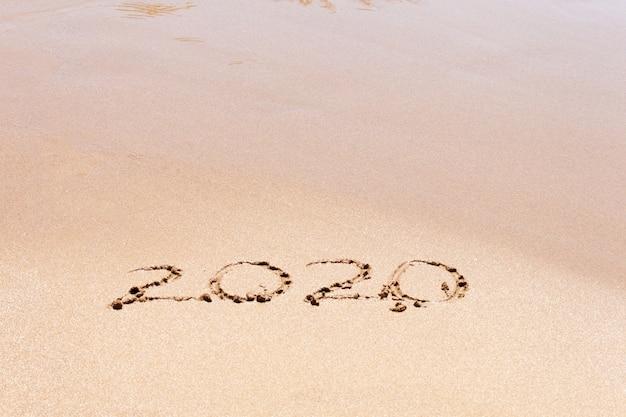 ビーチで幸せな新年2020年テキスト。休暇を計画しています。