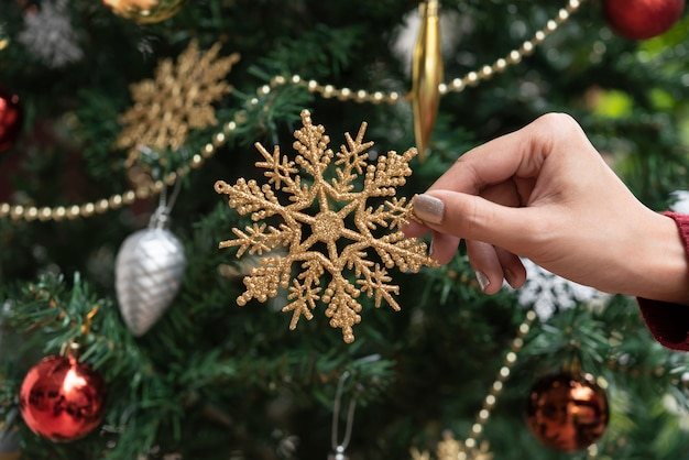 クリスマスツリーの背景に金の雪片の装飾を持っている手。クリスマスと新年あけましておめでとうございます2020。