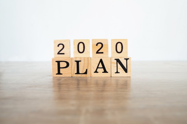木製のテーブルと白い背景上のテキスト「2020プラン」と木製のブロック。